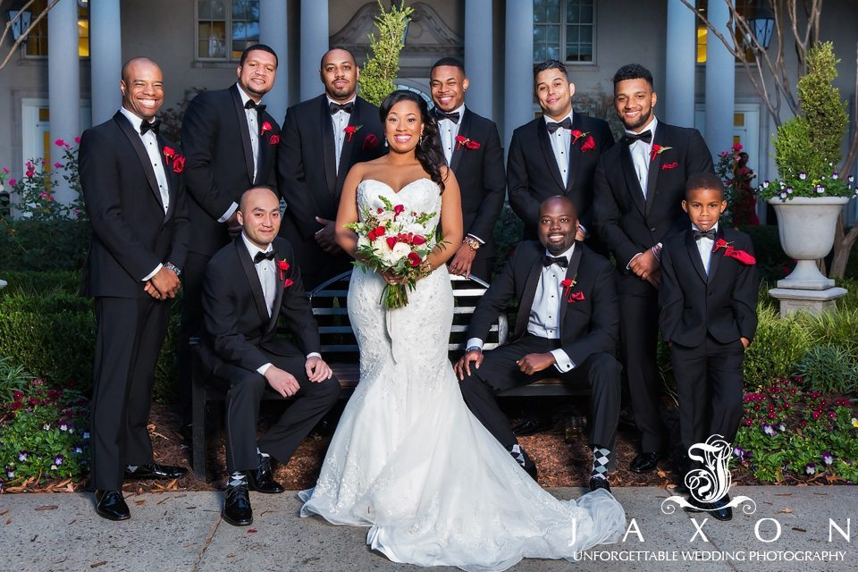 Bride wearing a Matthew Christopher strapless sweetheart gown, surrounded by nine grooms men in black tuxedos embellished with red boutonnieres and black bowtie.