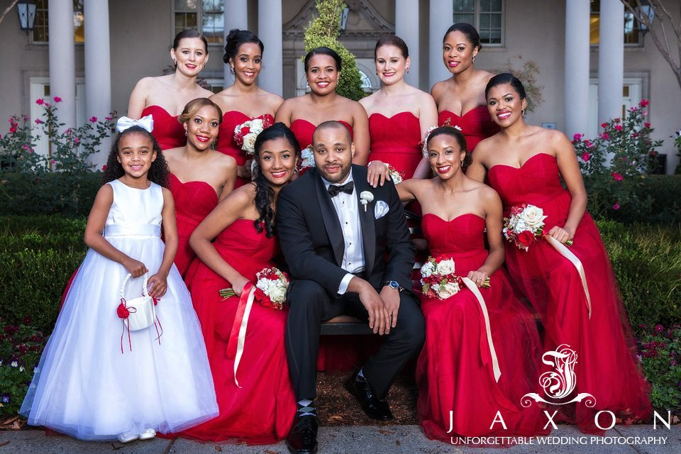 Portrait of groom in black tux, surrounded by nine bridesmaids in strapless long red dresses with bouquets of red and white roses and a flower girl in a white dress holding white basket in the garden at Biltmore Atlanta