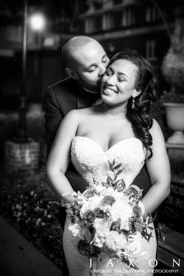 Black and white nighttime portrait of bride and groom embracing in the gardens at the Biltmore ballrooms in Atlanta