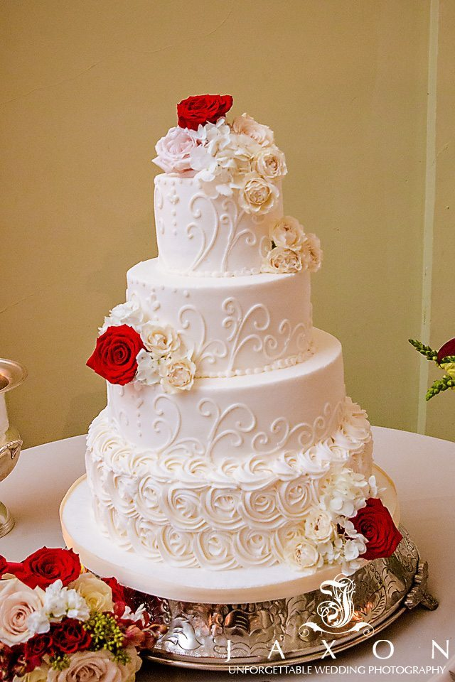 Flour tiered round white wedding cake topped with topped with red, pink and white roses