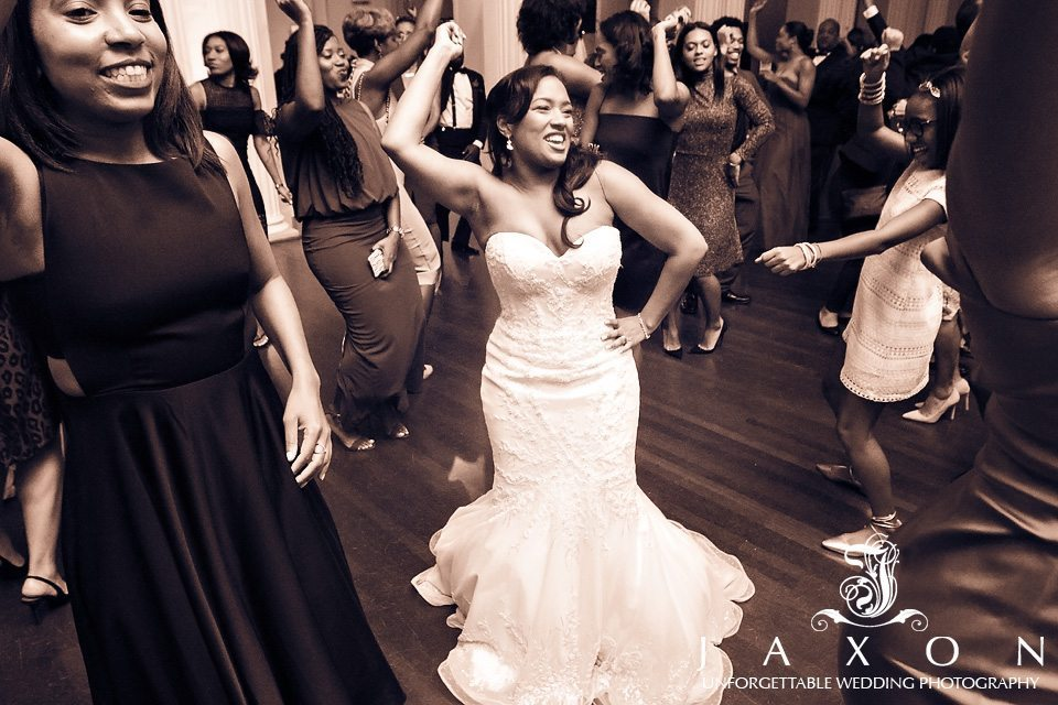 Sepia photo of bride dancing in the center of the dance floor surrounded by other dancers