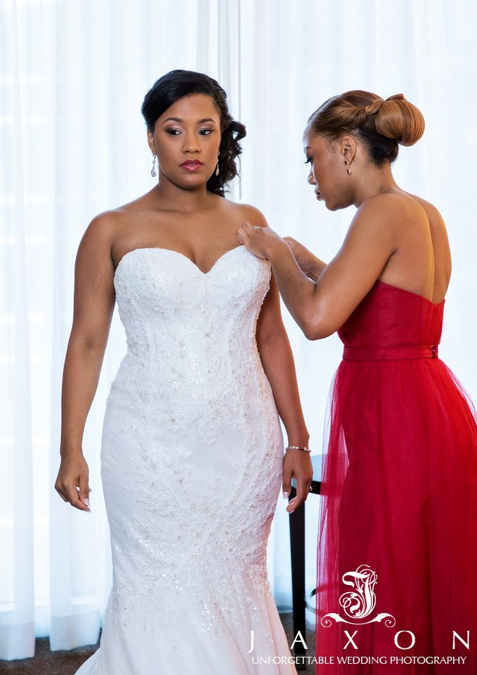 Front view of bride in crystal and milk beading and embroidery over dotted Swill tulle white Brielle trumpet wedding dress designed by Matthew Christopher. Attended to by bridesmaid in red dress at the Loews Hotel Atlanta