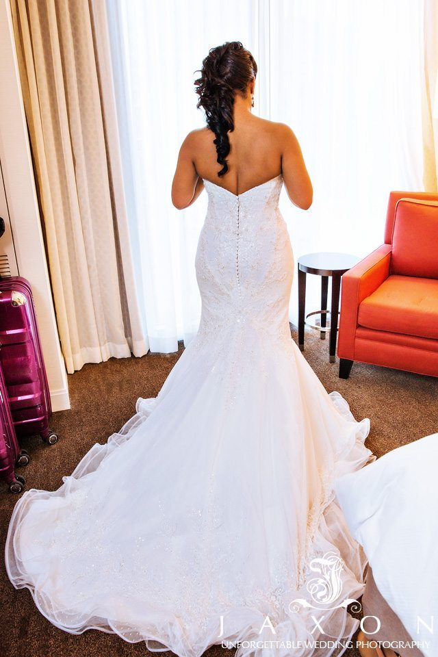 Bride in front of glass window showing off the train and back of her strapless Matthew Christopher designed trumpet, wedding gown with Swarovski crystal in her suite at Loews Hotel Atlanta