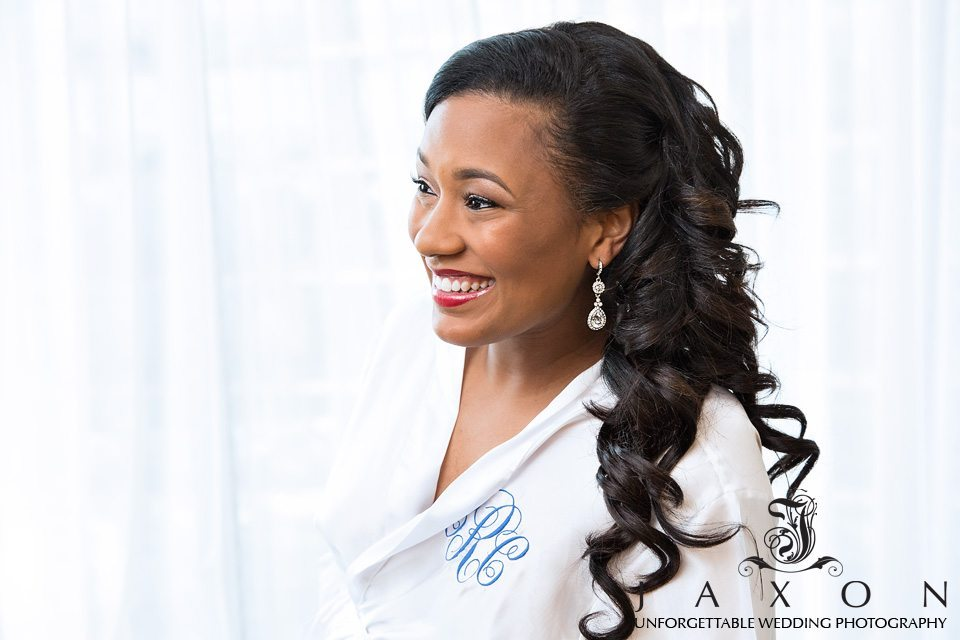 Profile portrait of bride with long curly hair wearing diamond chandelier earrings in her monogrammed white silk robe