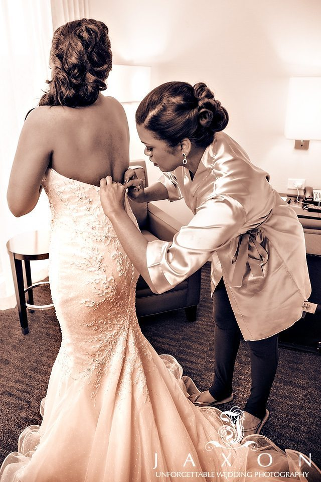 Sepia photo of bridesmaid helping bride button wedding dress in suite at Loews Hotel in Midtown Atlanta