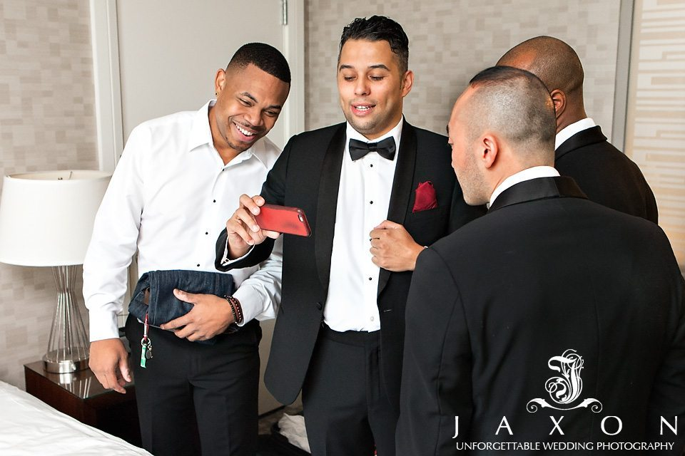 Groomsmen partially dressed in tuxes gather around a red phone in their suite before wedding for a game break