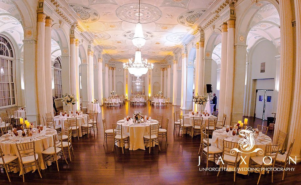 The double columned lined interior of the Georgian Ballroom designed with round tables topped with off-white tablecloths and napkins and multi layered candles surrounded by gold chiavari chairs with white cushions