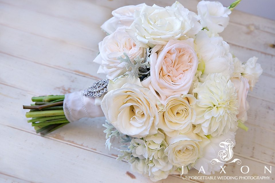 Brides bouquet made up of white , pink and off white roses, white hydrangea and dusty miller leaves