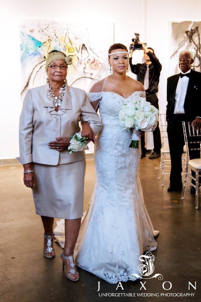 Bride escorted into the wedding ceremony wearing her ivory Symphony Rhapsody Wedding Dress