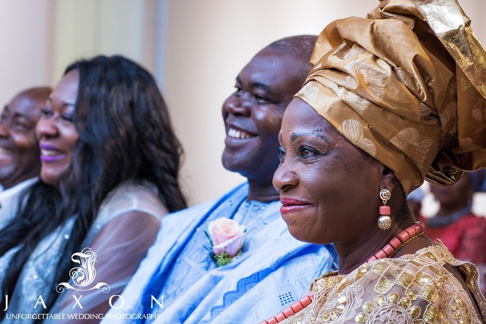 Guests in Nigerian cultural attire smiles during wedding ceremony