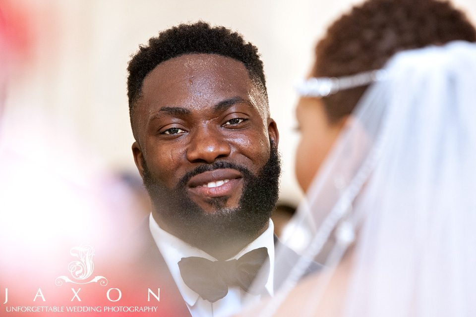 Smiling groom looks at his bride during wedding ceremony at Mason Fine Art