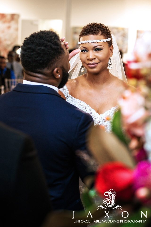 Bride mops the forehead of her perspiring groom during Mason Fine Art wedding
