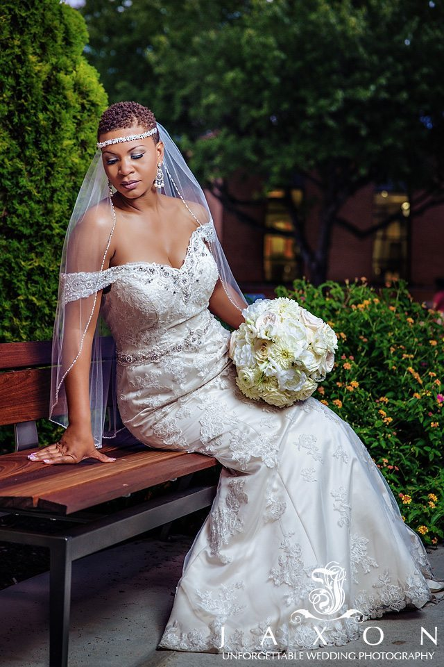 Portrait of Bride on park bench with bouquet in hand