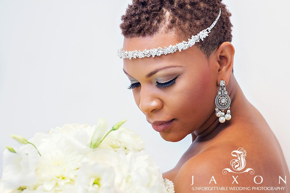 Bride with short hair cut and chandelier earrings leans into her rose filled bouquet
