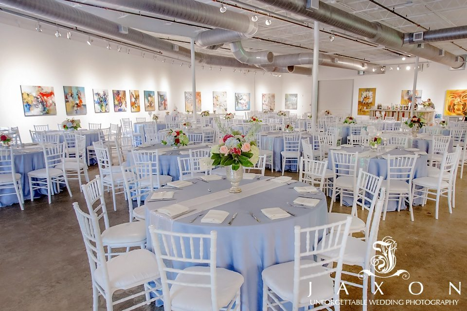 The event space at Mason Fine Art with white chairs and blue table covers