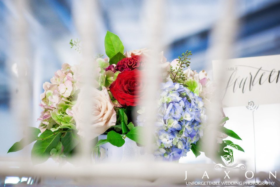 Photo of floral arrangement looking thru the rails of a white chair