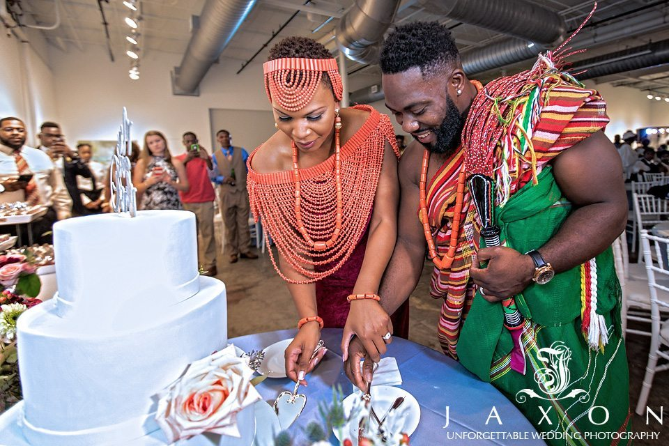Couple in Traditional Nigerian wedding outfit as they cut the wedding cake