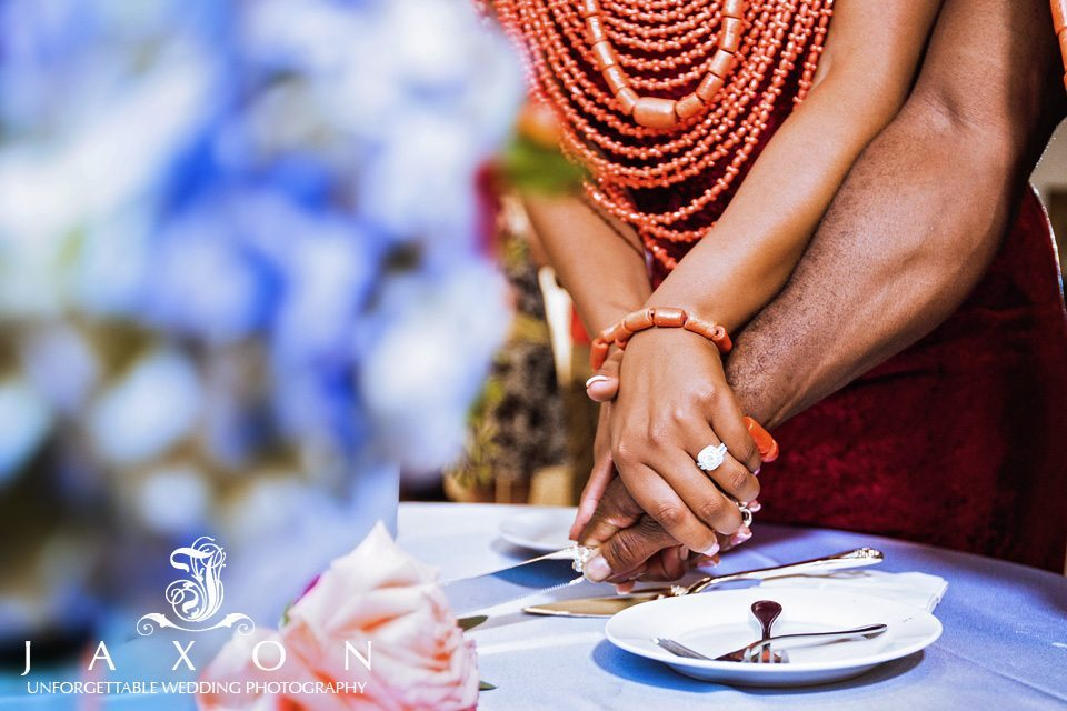 Close up of couple's hands as they cut the wedding cake