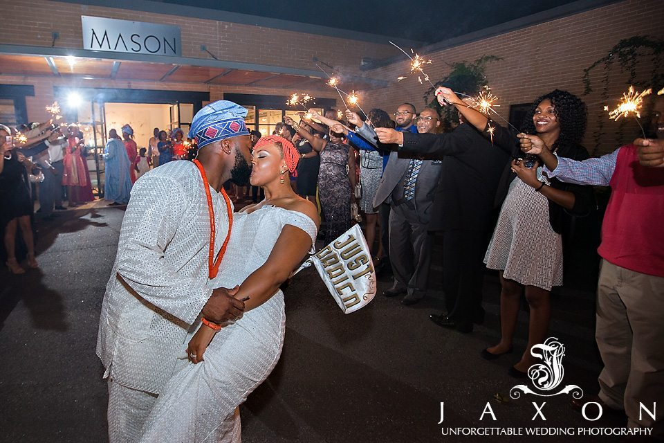 Groom kisses his bride while holding a just married sign