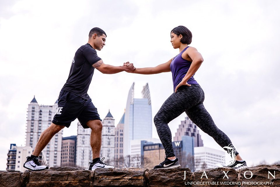 Couple in exercise gear working out at Piedmont Park with the midtown Atlanta skyline in background