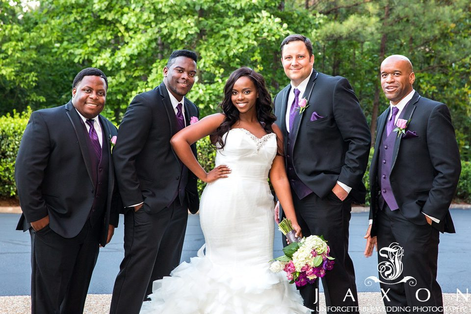 Bride poses with groomsmen in black tuxedos, plum vests and plum long ties ouside the DoubleTree by Hilton in Roswell