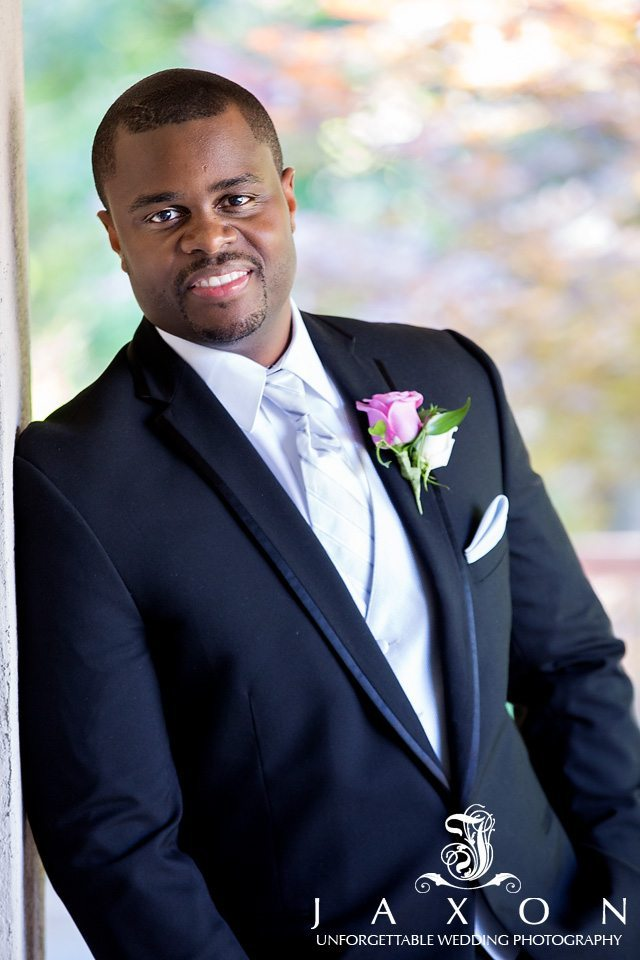 Dashing groom's lapel sports with a white and pink rose boutonnière
