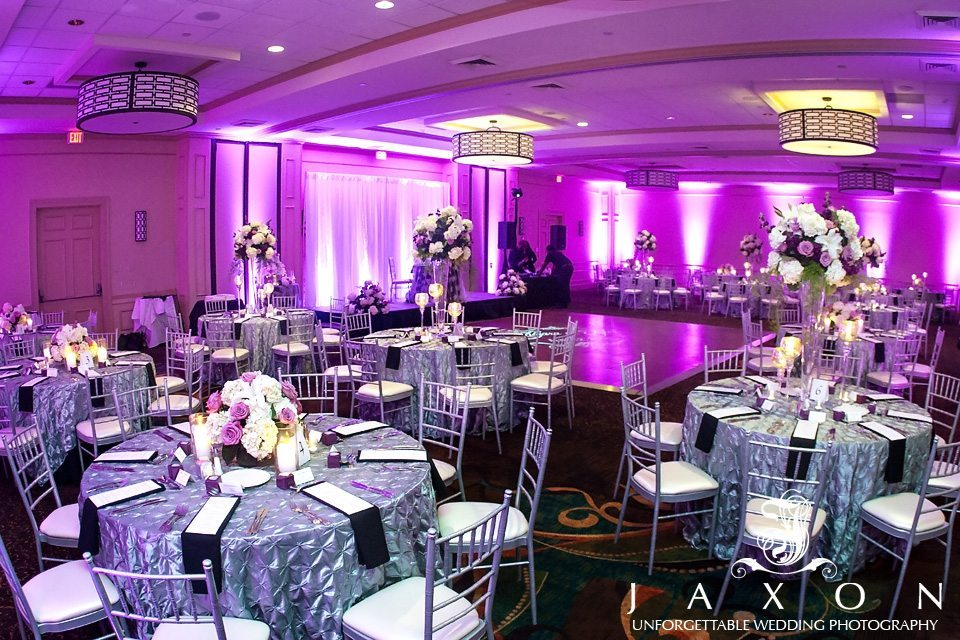 Silver draped tables with plum napkins surrounded by silver chiavari chairs with white cushions. The taples atr topped with tall vases of purple, plum and pink roses and hydrangeas