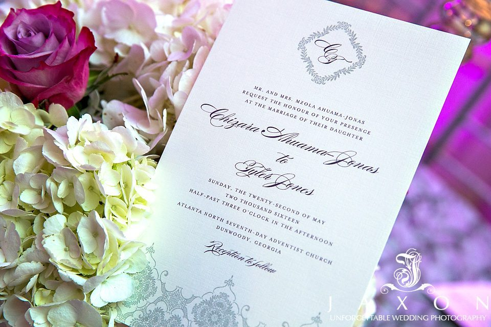 Wedding invite nestled amongst the bouquet of purple, plum and pink roses and hydrangeas