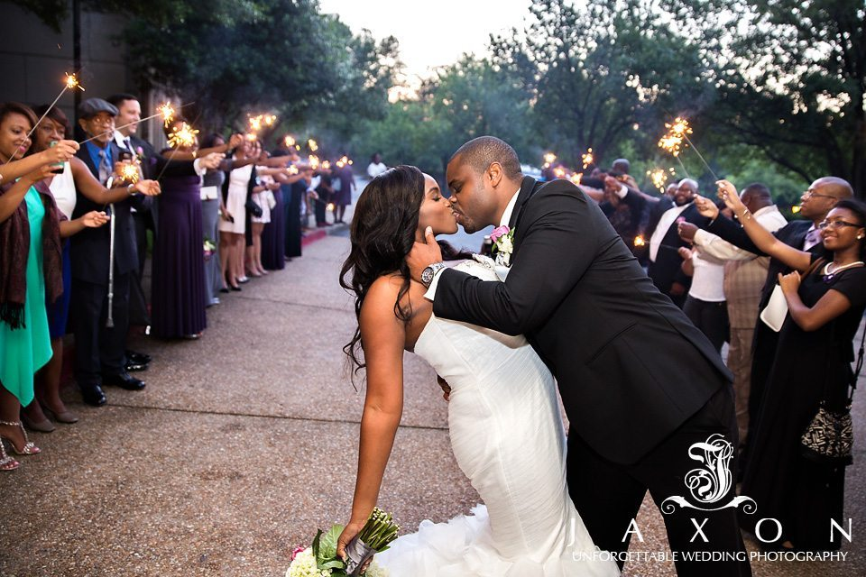 Guests holding sparklers line the walkway to the couple's car. He dips and kisses her as the crowd cheers them on.