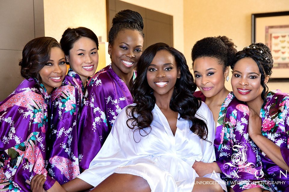 Bride and party in colorful plum colored silk robes before the DoubleTree Roswell wedding