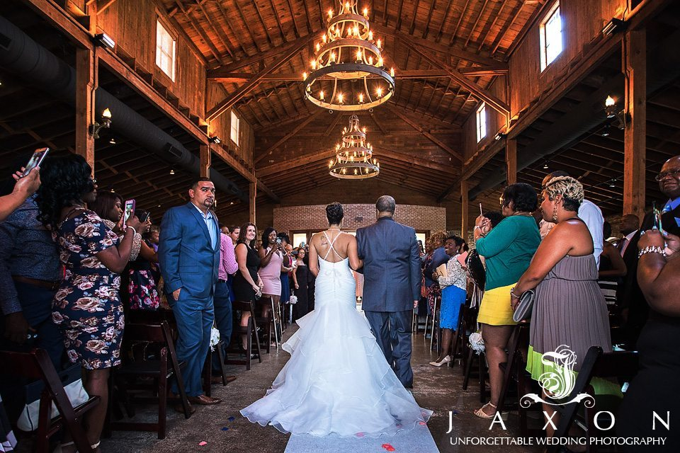 Bride escorted by dad into ceremony at 550 Trackside wedding under the three tiered round chandelier