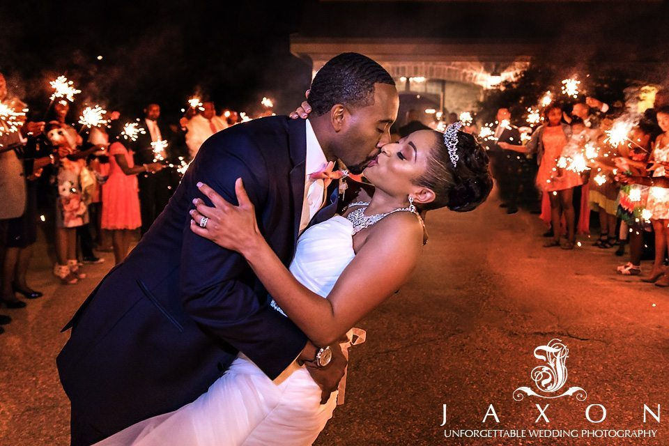 Newly weds kiss at the end of a row of sparklers  in the courtyard at of their 550 Trackside wedding